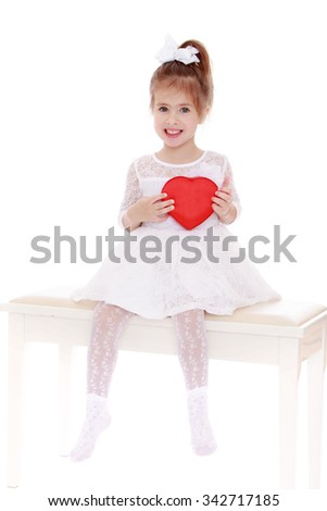 Adorable little Caucasian girl in a white dress sitting on white sofa, and holding a box of chocolates in the shape of a heart - Isolated on white background - stock photo