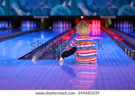 Adorable little child, blonde toddler girl, sitting on the floor at bowling club waiting for a strike - weekend family leisure concept - stock photo