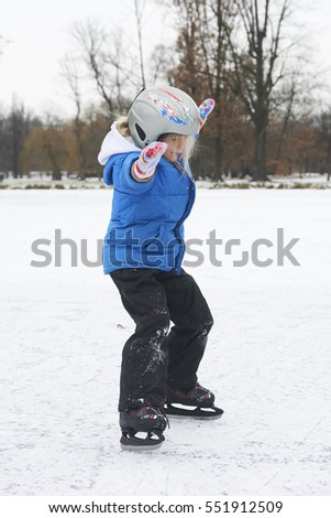 Adorable little child girl ice skating in winter snow day outdoors in the park on frozen pond. Wearing safety helmet