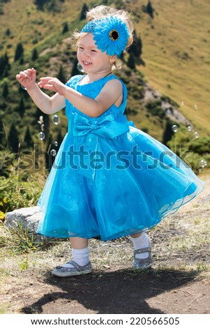 Adorable little child girl on grass on meadow. Summer green nature .  Use it for baby, parenting or love concept - stock photo