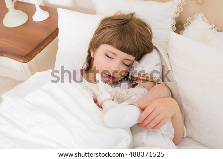 Adorable little child girl sleeping in the bed with her toy.