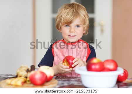 Adorable little child helping and baking apple pie in home''s kitchen, indoor. Filling apple with marzipan - stock photo