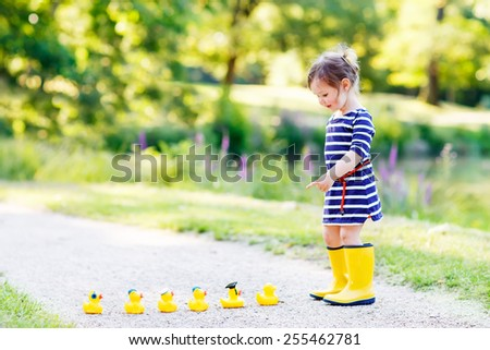 Adorable little child of 2 playing with yellow rubber ducks in summer park. Creative leisure with kids in forest on sunny day. - stock photo