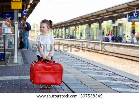 Adorable little child walking with big red suitcase on a railway station. Kid girl waiting for train and happy about a journey. People, travel, lifestyle concept - stock photo