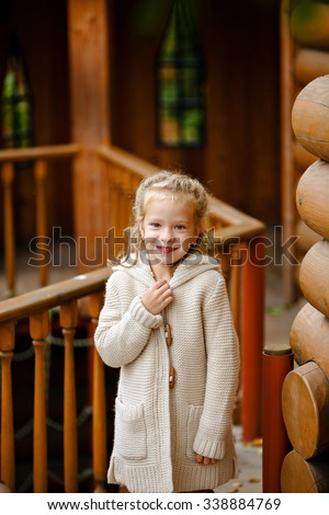 Adorable little curly blond girl in beige knitted sweater smiles slyly, against the background of a wooden house in autumn - stock photo