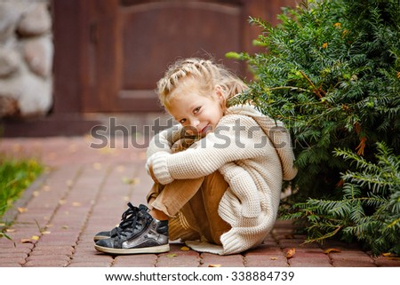 Adorable little curly blond girl in beige knitted sweater smiles slyly, sitting on a background of green fur-trees and house in autumn - stock photo