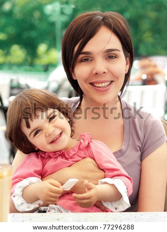 Adorable little daughter and mother smiling - stock photo