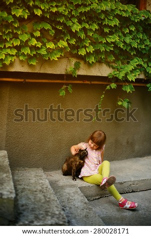 Adorable little girl and a cat outdoors - stock photo