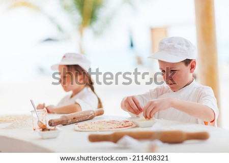 Adorable little girl and cute boy dressed as chefs making pizza - stock photo