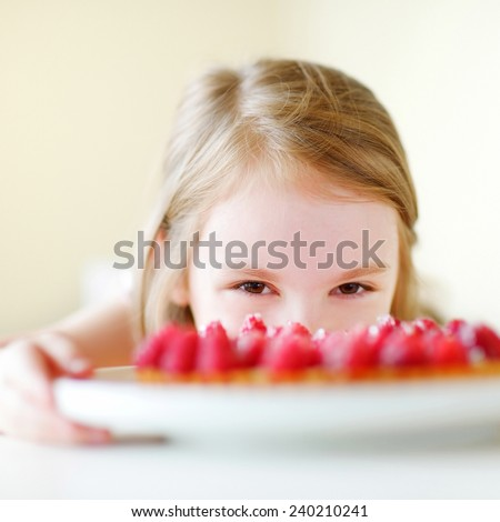 Adorable little girl and delicious raspberry cake - stock photo
