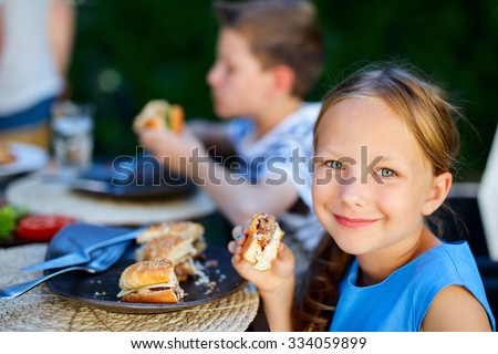 Adorable little girl and her family eating delicious homemade burger outdoors on summer day