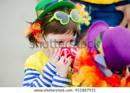 Adorable little girl and her sister in clown costume outdoors at summer day - stock photo