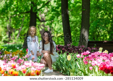 Adorable little girl and young mom enjoying warm day in tulip garden - stock photo
