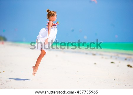 Adorable little girl at beach during summer vacation. Cute kid having fun jumping and enjoying her beach holidays - stock photo