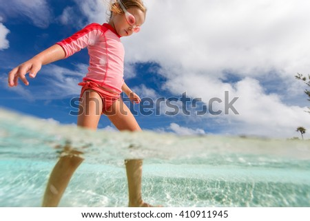 Adorable little girl at shallow water on tropical beach - stock photo