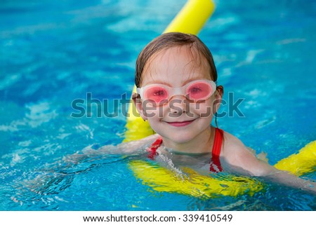 Adorable little girl at swimming pool having fun during summer vacation - stock photo