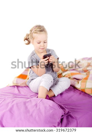 Adorable little girl awaked up in her bed,playing on the phone - stock photo
