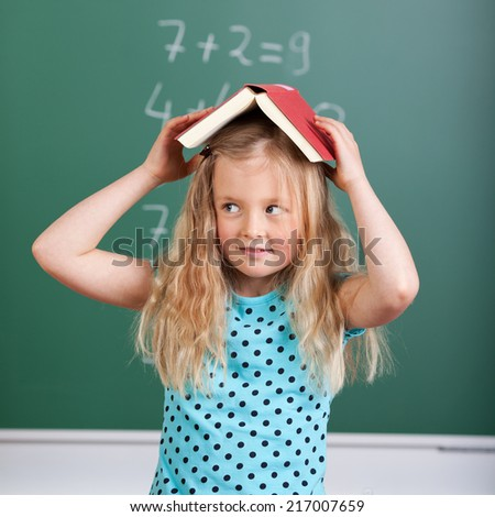 Adorable little girl balancing an open book on her head in school as she stands in front of the class blackboard looking to the side - stock photo