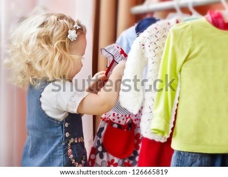 Adorable little girl choosing clothes - stock photo