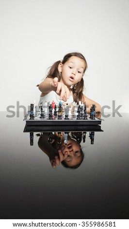 Adorable little girl concentrated playing chess - stock photo