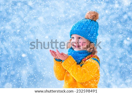 Adorable little girl, cute toddler in a blue knitted hat and yellow Nordic sweater, playing with snow catching snowflakes having fun outdoors in a beautiful winter park - stock photo