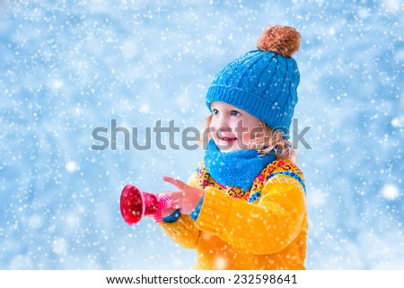 Adorable little girl, cute toddler in a blue knitted hat and yellow sweater, playing with Christmas toy bell,  catching snow flakes having fun outdoors in a beautiful winter park - stock photo