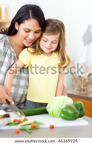 Adorable little girl cutting vegetables with her mother in the kitchen - stock photo