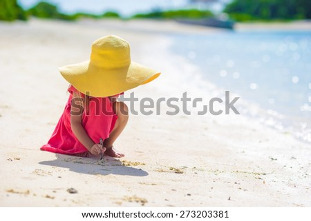 Adorable little girl drawing on white sand at the beach - stock photo