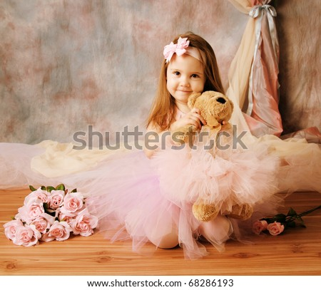 Adorable little girl dressed as a ballerina in a tutu, hugging a teddy bear sitting next to pink roses. - stock photo