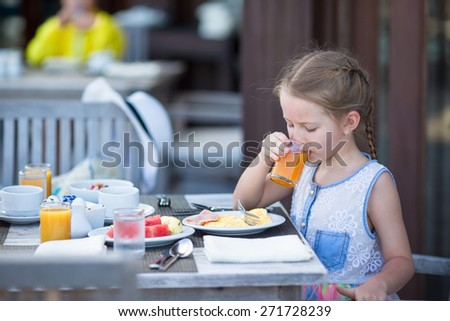 Adorable little girl drinking apple juice for breakfast in outdoor cafe - stock photo