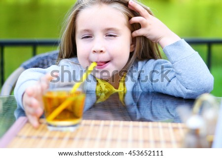 Adorable little girl drinking apple juice in cafe