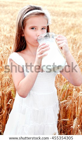 Adorable little girl drinking milk on field of wheat outdoor