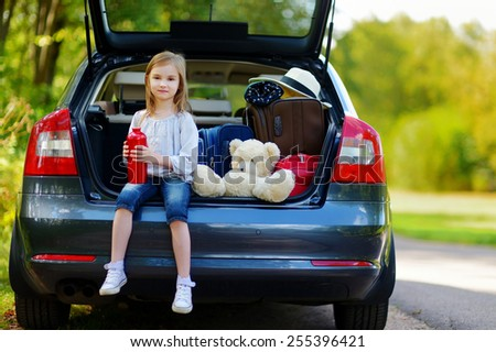 Adorable little girl drinking water before leaving for a car vacation with her parents - stock photo