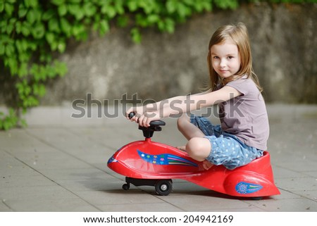 Adorable little girl driving a toy car outdoors on beautiful summer day - stock photo