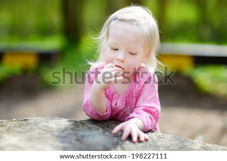 Adorable little girl eating a cookie outdoors - stock photo