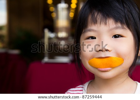 Adorable little girl eating a slice of orange with smiling face - stock photo