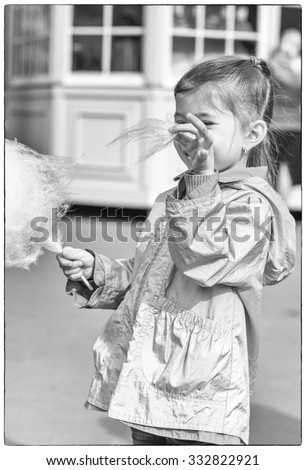 Adorable little girl eating candy-floss outdoors. Retro style. Selective focus  - stock photo