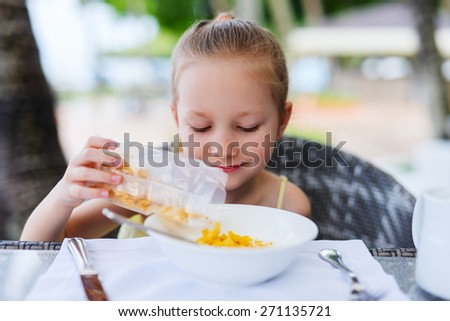 Adorable little girl eating cereal with milk for breakfast in restaurant - stock photo