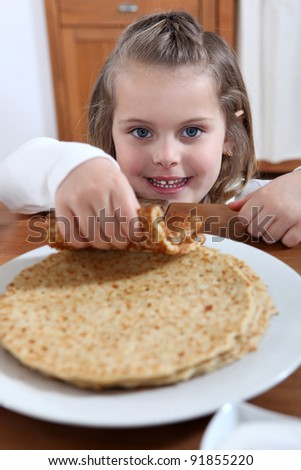 adorable little girl eating crepes - stock photo