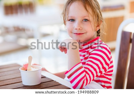 Adorable little girl eating ice cream - stock photo