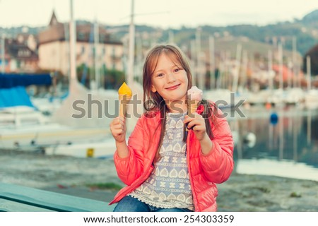 Adorable little girl eating ice cream outdoors, sunset - stock photo