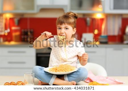 Adorable little girl eating spaghetti sitting on table - stock photo