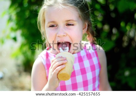 Adorable little girl eating tasty ice cream on summer day - stock photo