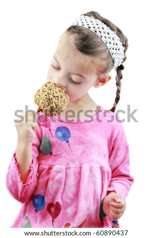 Adorable little girl eats a caramel apple against a white background.