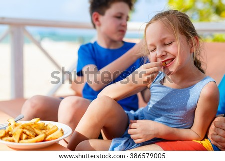 Adorable little girl enjoying eating french fries with her brother at outdoors restaurant on summer day - stock photo
