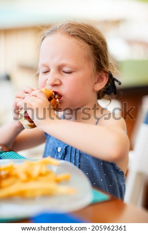 Adorable little girl enjoying eating hot dog for lunch at restaurant - stock photo