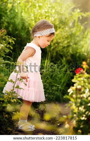 Adorable little girl exploring a beautiful garden - stock photo