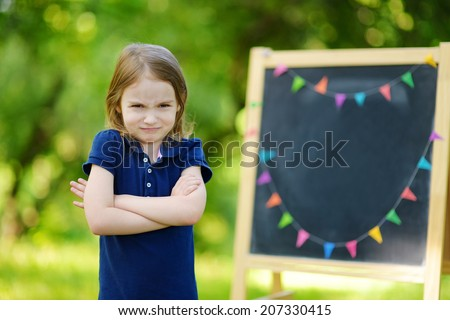 Adorable little girl feeling unhappy about going back to school - stock photo