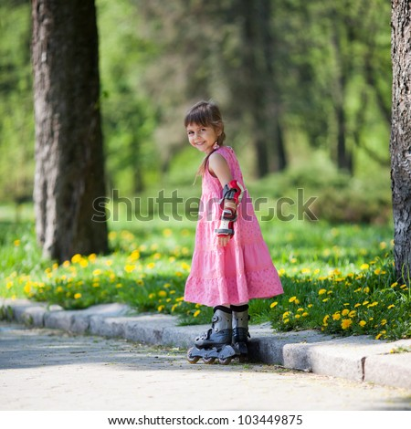 Adorable little girl gains confidence on her rollerblades - stock photo
