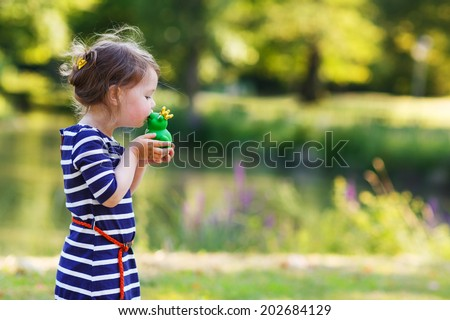 Adorable little girl giving a kiss to rubber frog. Outdoors. Fairytale concept - stock photo